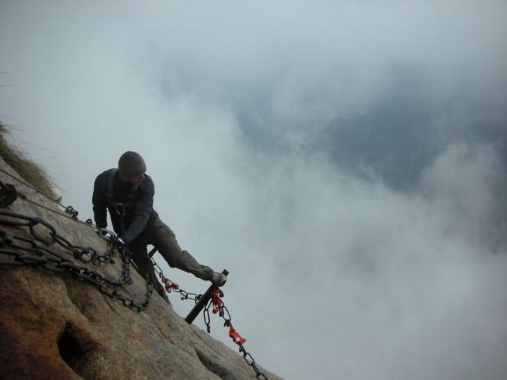 Hombre subiendo por una montaña hacia un monte en China
