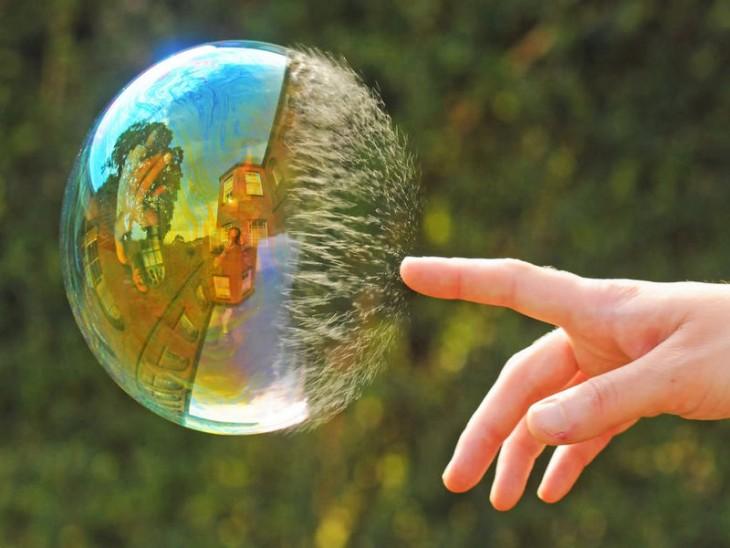 Imagen de una mano reventando una burbuja que pareciera que tiene photoshop