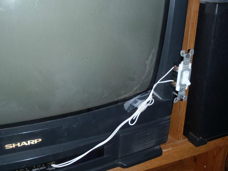televisión con un botón de encendido pegado a su lado derecho