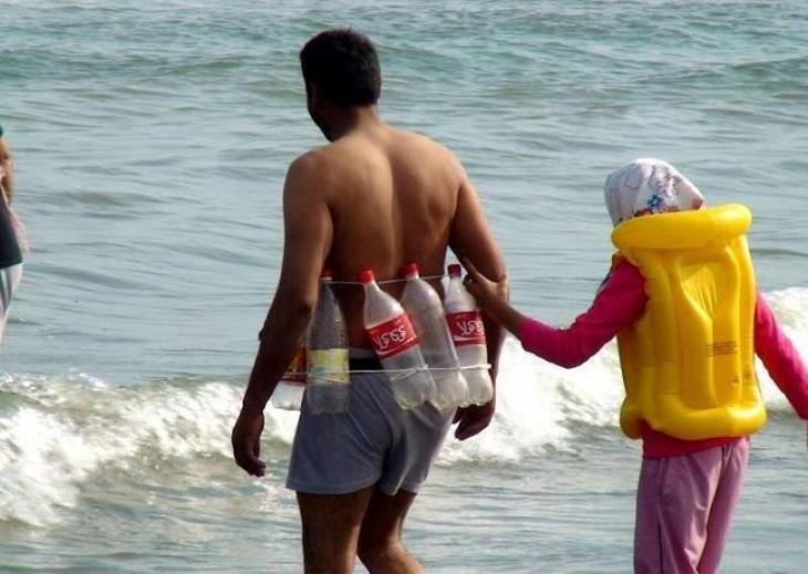 Niña sostenida del brazo de un hombre que lleva un chaleco hecho con botellas de refresco