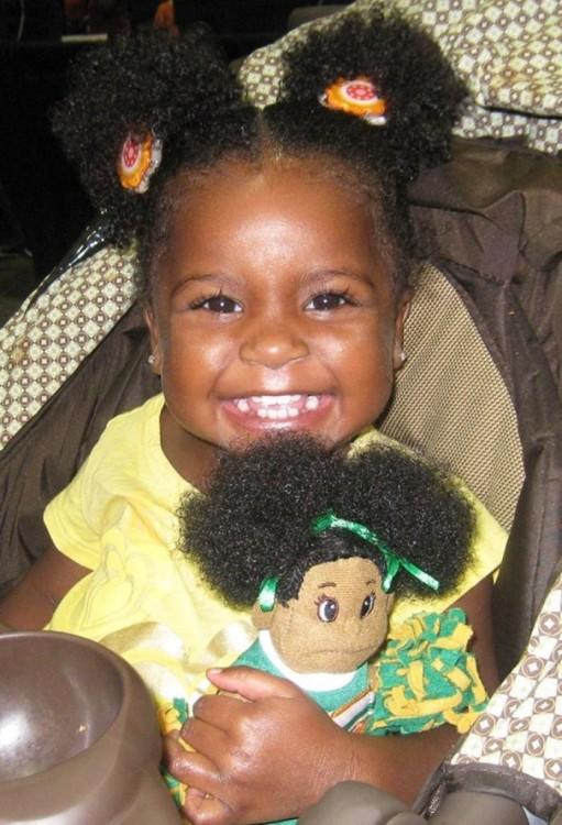 Niña en su carreola con su muñeca parecida a ella