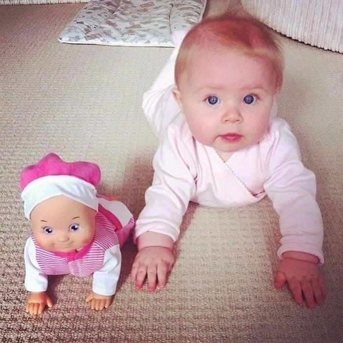 una muñeca junto a una bebe incadas sobre una alfombra