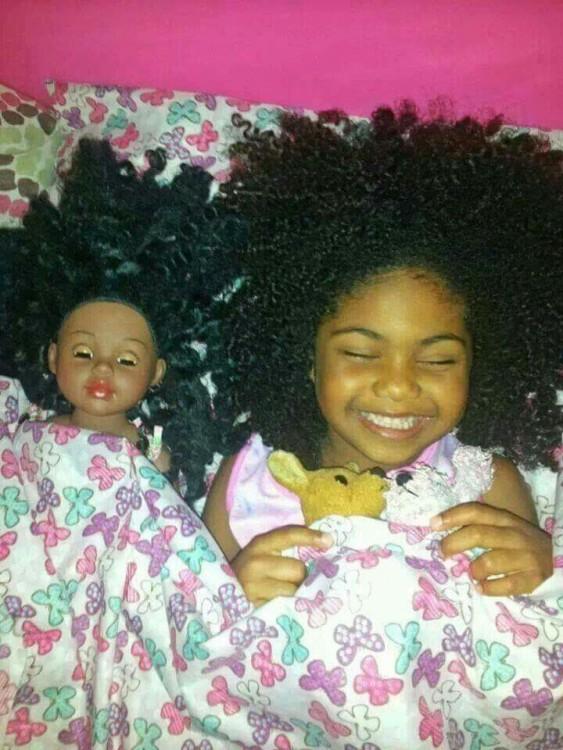 niña junto a su muñeca acostada sonriendo