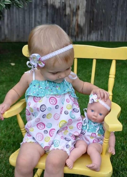 Niña sentada en una mecedora con su muñeca vestidas iguales