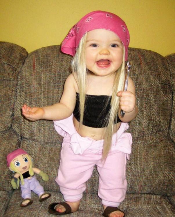 niña parada en un sillón con su muñeca