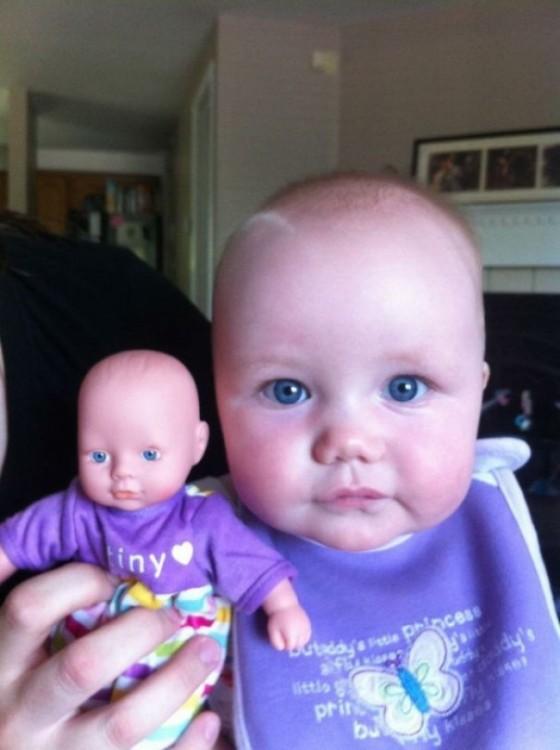 una bebé junto a su pequeña muñeca vestida igual a ella