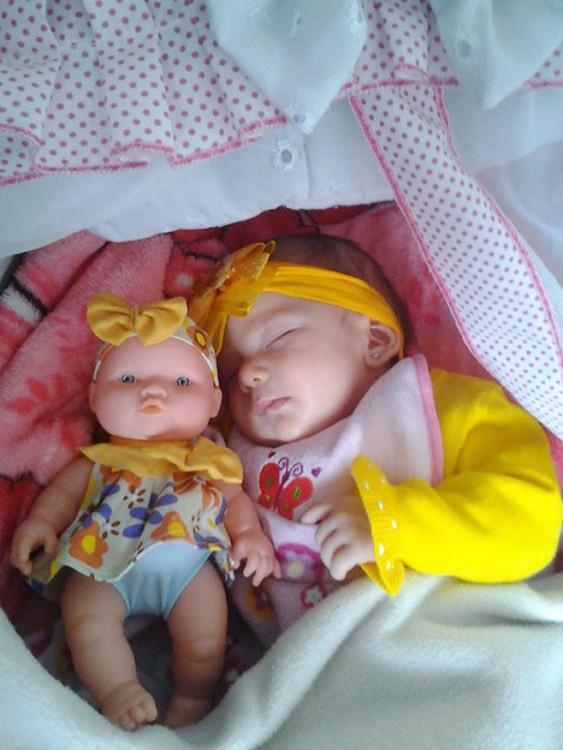 Bebé dormida junto a su muñeca vestida iguales