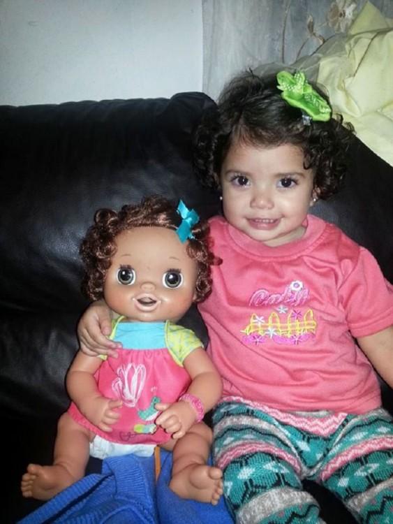 Muñeca que se parece a esta niña sentadas en la sala de una casa