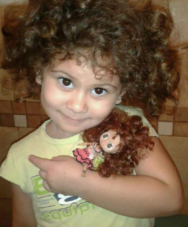 una pequeña niña abrazando a su muñeca