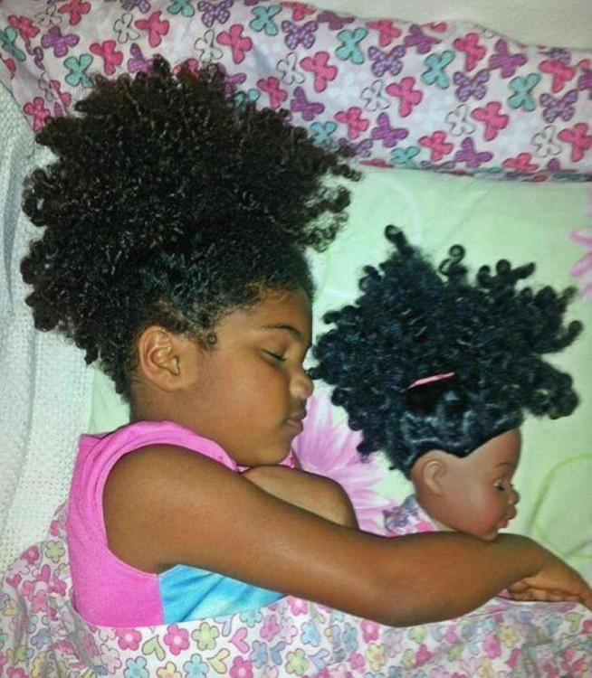 Niña igual a su muñeca acostadas en una cama