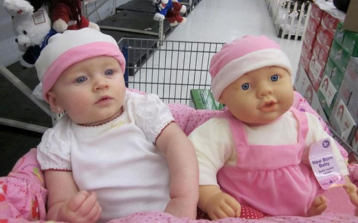 una bebé junto a su muñeca en el carrito de super mercado