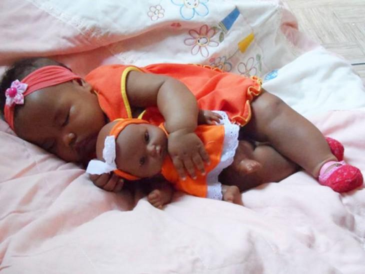 Bebé morenita acostada abrazando a su muñeca parecida a ella +