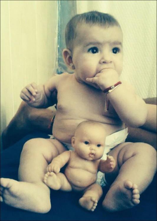 un bebé con su pañal y un pequeño muñeco entre sus piernas