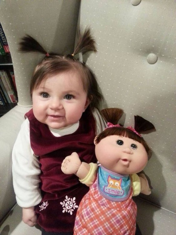 Niña con una muñeca sentada en un sillón