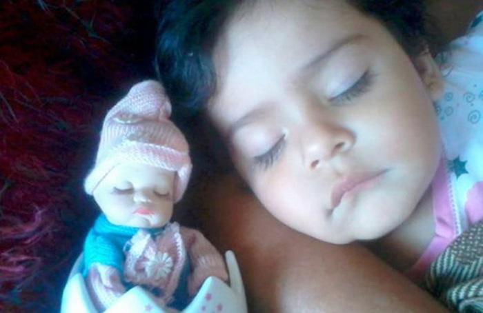 niña dormida junto a una muñeca parecida a ella