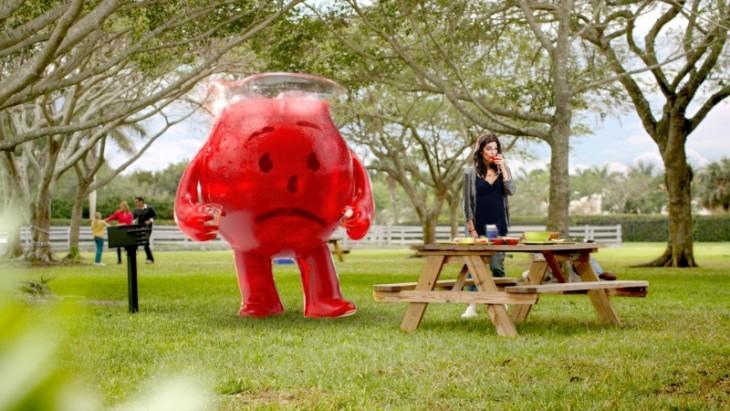 chica bebiendo su martini con una jarra de Kool-Aid a un costado en un jardín
