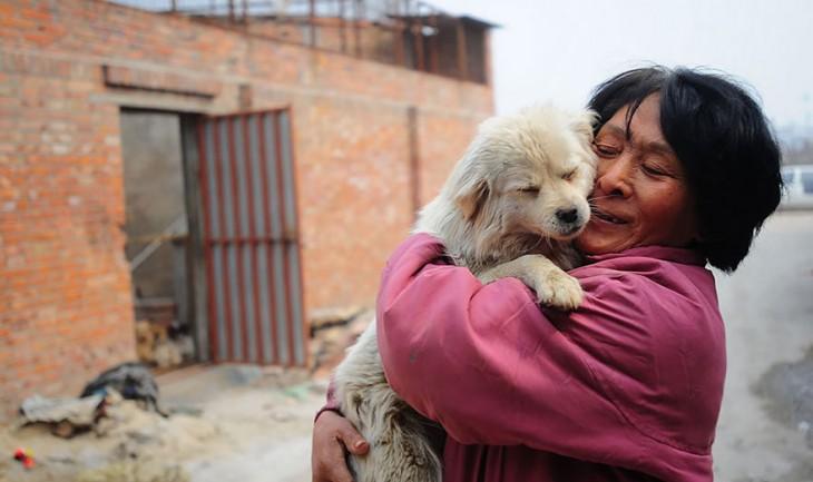 Una mujer en China abrazando a un perro que tiene en sus brazos