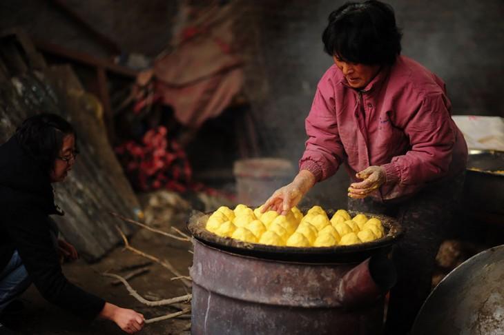Una mujer horneando pan con otra mujer colocando leña