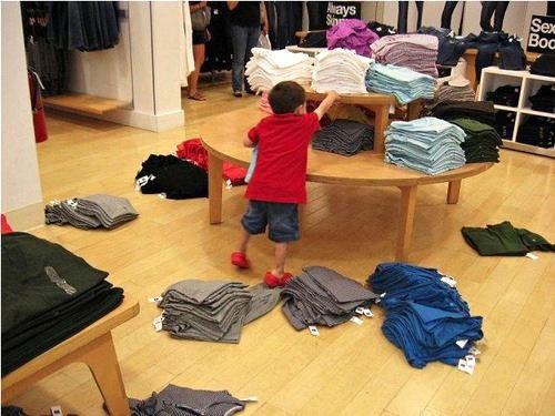 Niño tirando la ropa de un estante en el suelo en una tienda departamental
