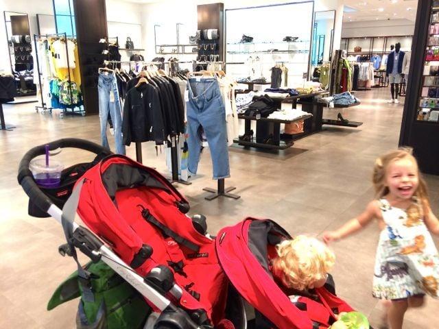 Un bebé dentro de una carriola en el centro comercial junto a una niña que sonrie