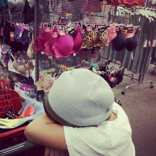 Niño recargado en el carro del super mercado con la cabeza hacia abajo