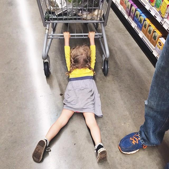 Niña arrastrada del carrito del super mercado