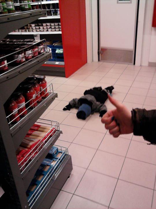 Un pequeño niño acostado en el suelo de un super mercado