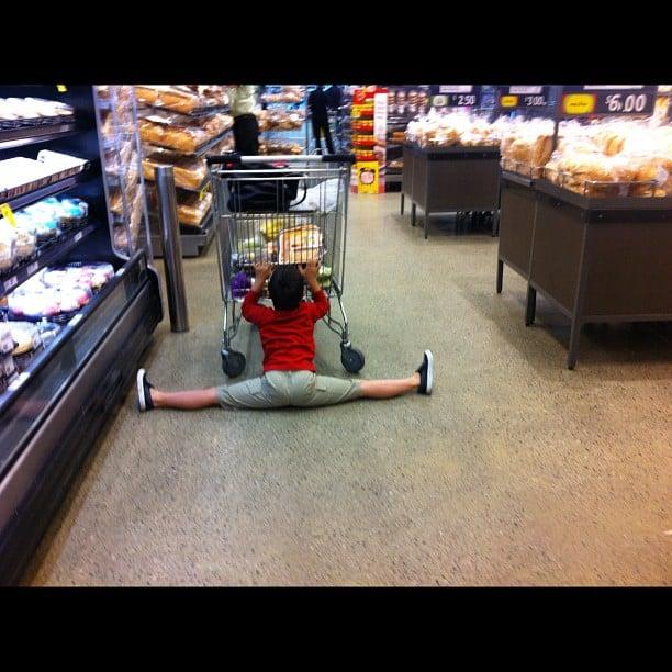 Un niño abierto de pies sosteniendo el carrito del super mercado
