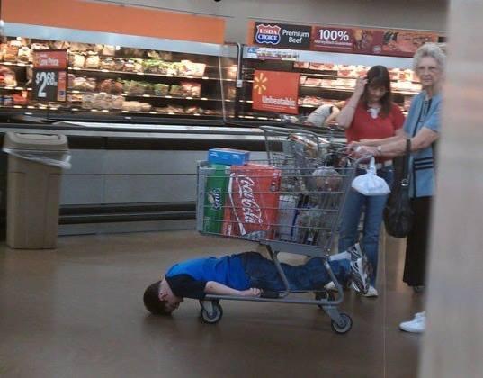 Niño dentro de la parte inferior de un carrito en el centro comercial