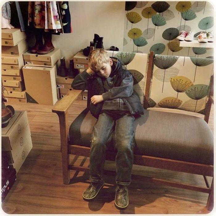 Niño sentado en un sillón dormido esperando a su mamá en la zapatería