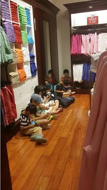 Niños sentados en el suelo en un centro comercial entretenidos con los celulares