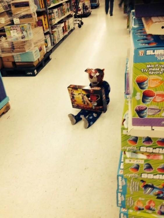 Niño sentado en el piso del centro comercial con un juguete en sus piernas