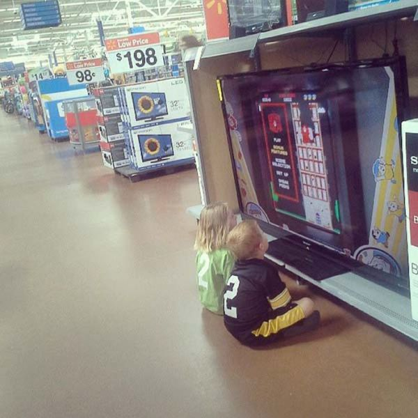 Niños jugando en el centro comercial sentados en el suelo