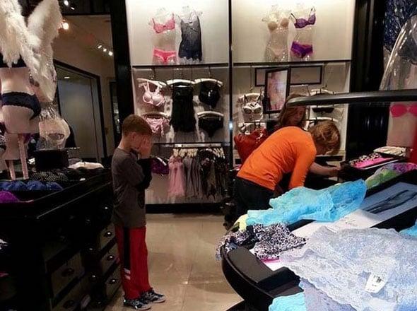 Niño tapándose los ojos frente a sus mamá eligiendo ropa