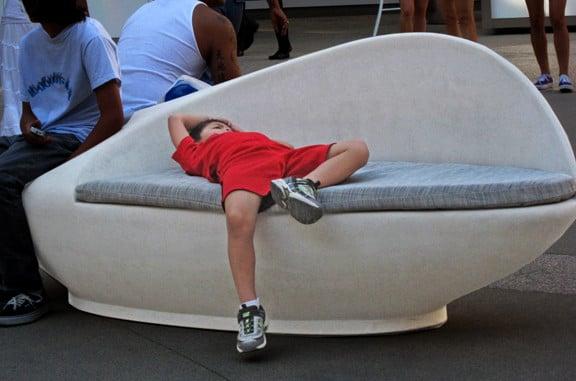 Niño acostado en un sillón esperando a que su mamá termine de hacer las compras
