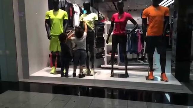 Dos niños frente a los maniquis de una tienda de deportes