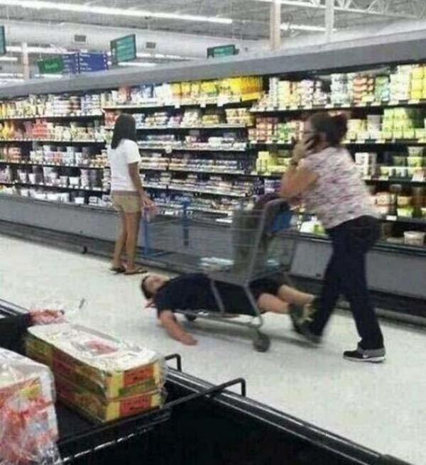 Un niño acostado en la parrilla debajo del carrito del super mercado