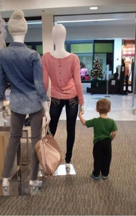 Niño sosteniendo la mano de un maniqui en la puerta del centro comercial