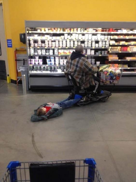 Niño que esta siendo arrastrado por el carrito de su abuelo en el centro comercial