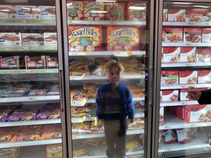 Niño dentro un congelador en el super mercado