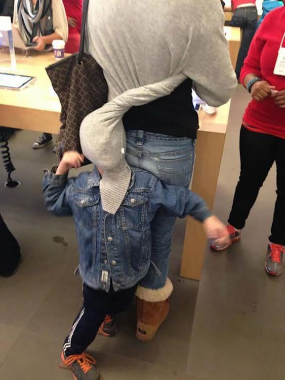 Niño en la parte trasera de su mama atorado en su suéter