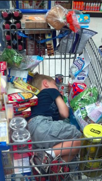 Niño dormido en el carrito del centro comercial en medio de todas las compras