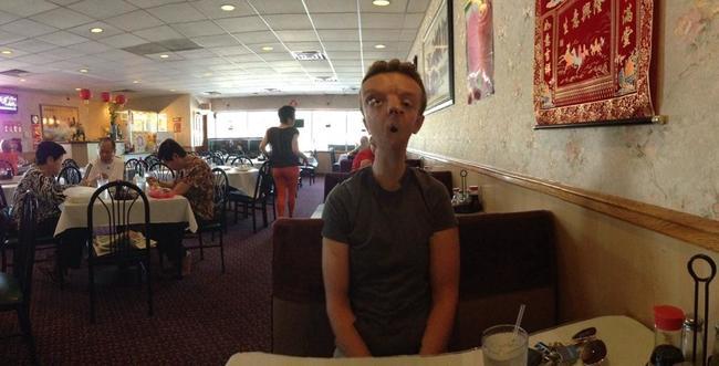 Fotografía panorámica que salio mal de un chico en un restaurante chino