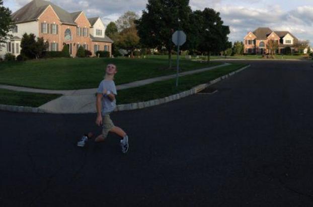 fotografía panorámica de un chico que va por la calle medio doblado