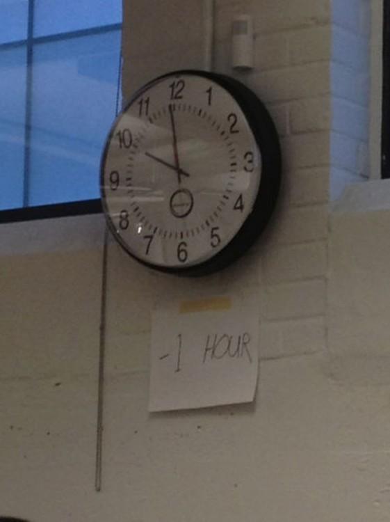 Reloj de pared con un recado pegado debajo de él