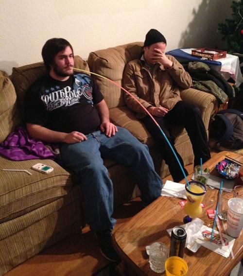 Chicos sentados en un sillón con una mesa frente a ellos donde uno de ellos tiene un gran popote hasta su bebida
