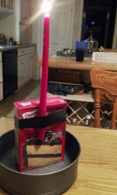 Caja de un pastel sobre una base redonda con una vela sostenida con una cinta de color negro