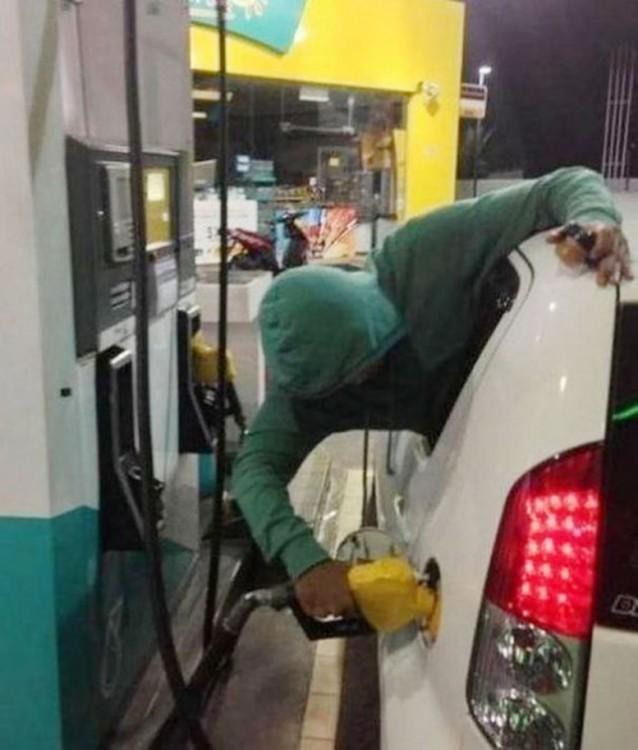 Hombre saliendo por la ventana de un coche despachándose gasolina solo