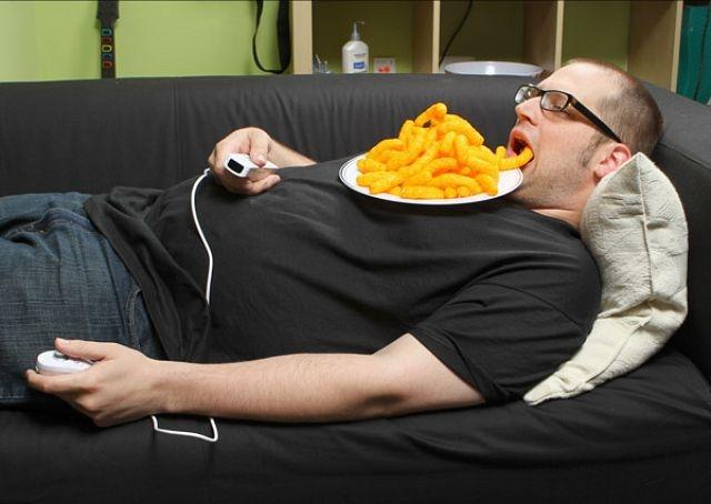 hombre acostado comiendo chetos desde su pecho hasta su boca