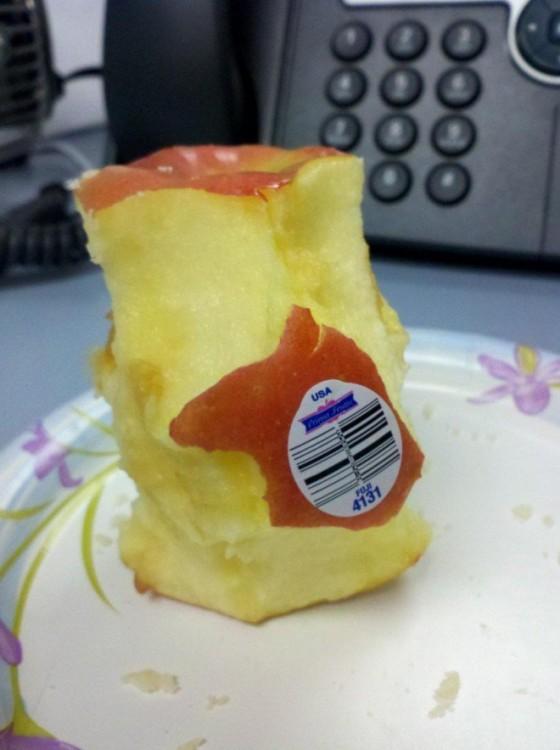 una manzana mordida con un pedazo de papel pegado
